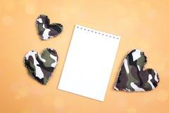 打开有军事心脏的空白的笔记本在黄色背景 C 免版税库存照片