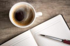 打开有咖啡杯的空的笔记本 免版税图库摄影