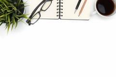 打开有咖啡杯的螺旋空白的笔记本在白色书桌上 免版税库存照片