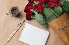 打开有咖啡的空的笔记本、r刷子和花束  库存图片