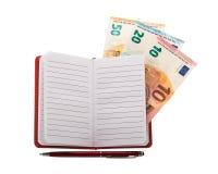 打开有圆珠笔和欧洲钞票的笔记本 免版税库存图片