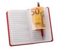 打开有圆珠笔和滚动的欧洲钞票的空白的笔记本 免版税库存照片