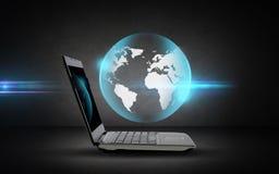 打开有地球投射的便携式计算机 免版税图库摄影
