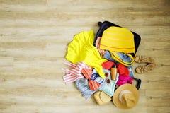 打开有堆的手提箱在地板上的展开的衣物 热带假期概念的妇女包装 倍数被打开的女性c 免版税库存图片