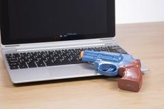 打开有小玩具枪的膝上型计算机 免版税库存照片