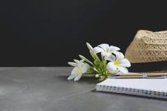 打开有帽子的笔记本 书开放,与笔和花在桌上 免版税库存图片
