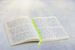 打开有手写的lorem ipsum文本和丝带书的笔记本 库存图片