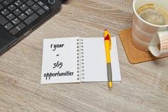 打开有文本`的笔记本一年365机会`和一杯咖啡在木背景的 免版税库存照片
