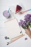 打开有杯子的空的笔记本越桔奶昔,乳酪蛋糕s 图库摄影
