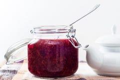 打开有果酱和金属匙子的玻璃容器 免版税图库摄影