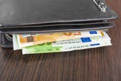 打开有欧洲现金的钱包10 20 50 100在木背景 人有现金欧元的` s钱包 免版税库存图片