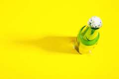 打开有泡沫的啤酒瓶在与边界的黄色背景 库存图片