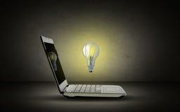 打开有电灯泡的便携式计算机 免版税库存图片