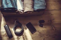 打开有男性衣裳的手提箱在木地板上的旅行的 免版税库存照片