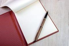 打开有白页和金钢笔的笔记本 免版税库存照片