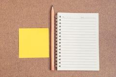 打开有稠粘的笔记和铅笔的笔记本 库存照片