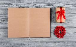 打开有空白页、红珊瑚小珠和一点礼物盒的笔记本有弓的 木背景 顶视图 平的位置 免版税库存照片