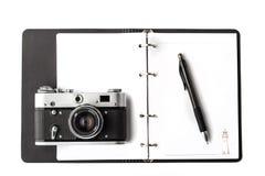 打开有笔和照相机的清楚的笔记本 库存图片