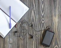 打开有笔和电话的空的笔记本 图库摄影