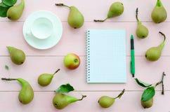 打开有绿色笔、咖啡杯和梨的笔记本 库存图片