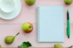 打开有绿色笔、咖啡杯和梨的笔记本 免版税库存照片