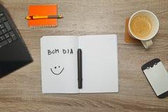 打开有葡萄牙人词` BOM DIA `你好的笔记本和一杯咖啡在木背景的 图库摄影