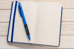 打开有蓝色盖子的在木背景的笔记本和笔 免版税库存照片