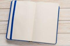 打开有蓝色盖子的笔记本在木背景 免版税图库摄影