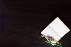 打开有钮扣眼上插的花的笔记本和在黑暗的木背景的角落的绿色铅笔 库存照片