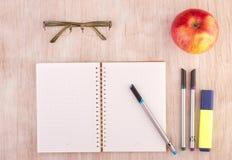 打开有铅笔、玻璃和苹果的笔记本在书桌上 免版税库存照片