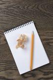 打开有铅笔削片的笔记本在橡木桌上 免版税库存照片
