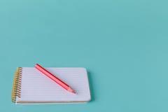 打开有铅笔的螺旋空白的笔记本在蓝绿色书桌背景 免版税库存照片