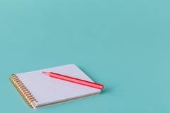 打开有铅笔的螺旋空白的笔记本在蓝绿色书桌背景 免版税库存图片