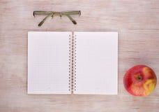 打开有玻璃的在书桌上的笔记本和苹果 图库摄影