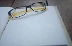 打开有玻璃的空的笔记本在木桌上 免版税库存图片