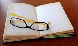 打开有玻璃的空的笔记本 免版税库存照片