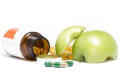 打开有绿色苹果计算机的医学瓶 免版税库存照片