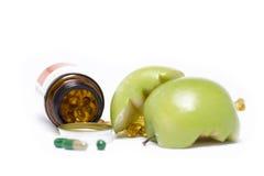 打开有绿色苹果计算机的医学瓶 免版税库存图片