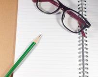 打开有绿色铅笔、镜片和被排行的页的空的笔记本 库存图片