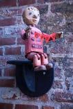 打开标志;在砖墙上的德国男孩小雕象 库存照片