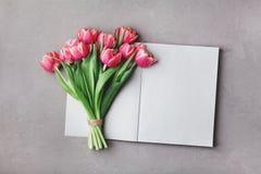 打开桃红色郁金香花空的笔记本和花束在灰色石台式视图的在舱内甲板位置样式 妇女运转的书桌 免版税库存图片