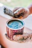 打开桶蓝绿色油漆在手上 库存照片