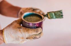 打开桶蓝绿色油漆在手上 库存图片