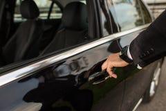 打开汽车大型高级轿车门的人 图库摄影