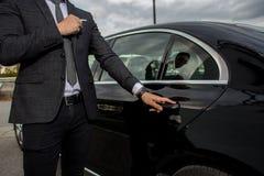 打开汽车大型高级轿车门的人 免版税库存图片