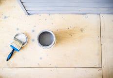 打开油漆罐头和一把刷子在地板上 库存照片