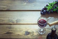 打开瓶与葡萄酒杯、拔塞螺旋和成熟葡萄的红葡萄酒在木板 复制空间和顶视图 免版税库存图片
