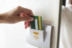 打开电灯旅馆ro的女性手插入物室卡片钥匙 免版税库存照片