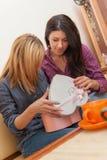 打开礼物的两个女孩 免版税库存照片