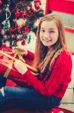打开礼物的十几岁的女孩 库存图片